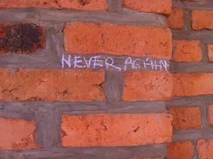 """Writing on Rwandan brick wall: """"Never Again"""""""